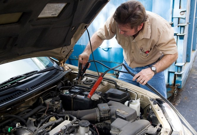 Auto mechanic using jumper cables to charge a car battery.